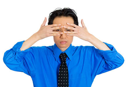 Closeup portrait of young man covering face with hands with just enough space to peek through, isolated on white background. Negative emotion facial expression feelings, reaction. Media journalism spy photo