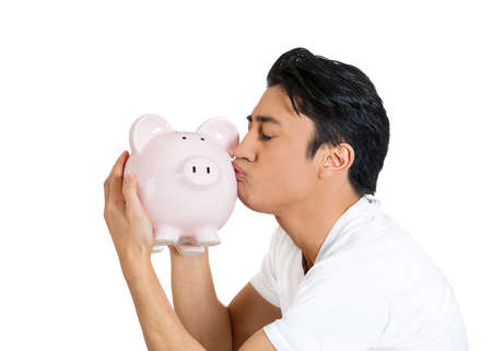 college fund savings: Closeup side view profile portrait of young happy successful enthusiastic affectionate sensitive man kissing piggy bank, isolated on white background. Financial decisions, money savings, college fund