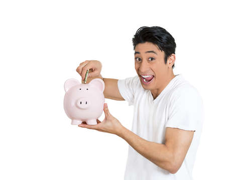 Closeup portrait of young smiling school man depositing money into piggy bank, isolated on white background. Smart currency financial investment wealth decisions. Budget management and savings photo
