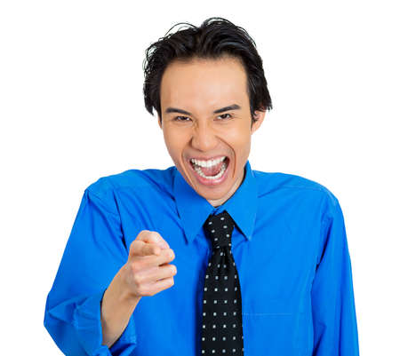 humiliation: Closeup portrait of young business man laughing, pointing with finger at someone, something isolated on white background. Positive human face expression, emotion, feeling, attitude, approach, reaction