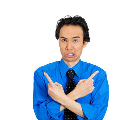 ambiguous: Closeup portrait of confused young man pointing in two different directions, not sure which way to go in life, isolated on white background. Negative emotions, facial expressions, feelings, dilemma Stock Photo