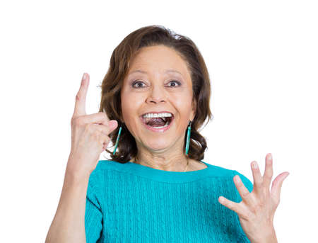 Closeup portrait of smiling pretty senior mature woman pointing with index finger up aha having the right answer, isolated on white background.