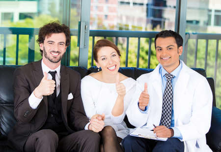 Closeup portrait of smiling health care professional, doctor,  nurse planning and showing thumbs up with happy young successful couple on black couch in office, isolated on city urban background photo