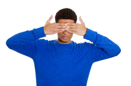 withhold: Closeup portrait of young male handsome man closing covering eyes with hands cant see and hiding, isolated on white background. See no evil concept. Negative human emotions facial expression feelings