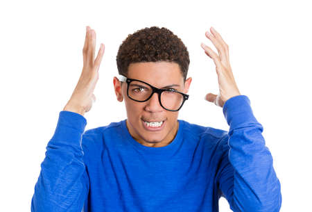 messed up: Closeup portrait of frustrated, angry nerdy man with hands raised and glasses messed up on face, showing bare teeth, isolated on white background. Stock Photo