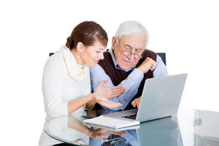 savvy: Closeup portrait of young technology savvy, frustrated woman showing confused senior older elderly man with eyeglasses how use laptop isolated on white background. Generation gap difference concept