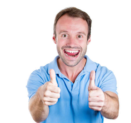 Closeup portrait of handsome super happy excited young smiling man giving two thumbs up sign at camera isolated on white background. Positive human emotion, facial expression, feelings. Symbols, signs photo