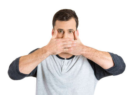 repress: Closeup portrait of young man covering closed mouth, open eyes. Speak no evil concept, isolated white background. Negative human emotions, facial expressions signs and symbols. Media news coverup Stock Photo