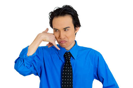 miscommunication: Closeup portrait of angry annoyed young single man, upset student, worker making call me gesture, sign with hand shaped like phone isolated on white background. Negative human emotion, face expression