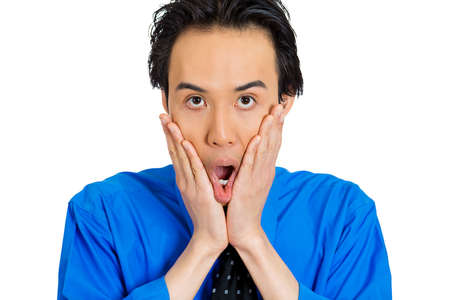 full face: Closeup portrait of surprised, shocked, stunned young man, worker, employee, in full disbelief hands on face, isolated white background. Human facial expressions, emotions, reaction, perception Stock Photo