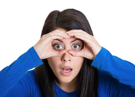 corporate espionage: Closeup portrait of young, curious funny woman, looking through fingers like binoculars, searching for something, surprised, shocked by what is waiting her in the future isolated, white background