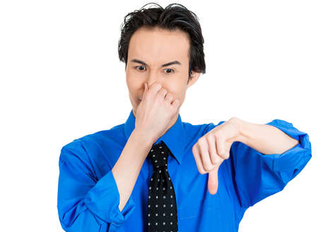 stinks: Closeup portrait of angry, mad, pissed off man, giving thumbs down something stinks gesture, looking with negative facial expression, disapproval, isolated on white background. Human emotions signs Stock Photo