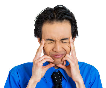 deeply: Closeup portrait of unhappy, sad, thoughtful, young business man thinking deeply, bothered by mistakes, hands on head, having headache isolated on white background. Negative emotion facial expressions