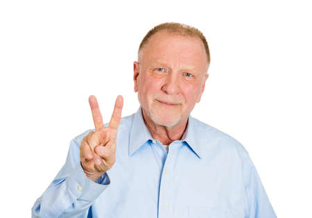 Closeup portrait of senior, smiling business man, holding up peace, victory, two sign, isolated on white . Positive emotion, facial expressions, symbols, attitude communication. Life success photo