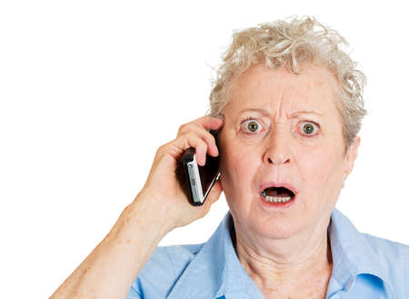 unsettled: Closeup portrait stressed shocked elderly business woman, senior lady talking on cellular, having unpleasant conversation receiving bad news isolated white . Human emotion, facial expression Stock Photo