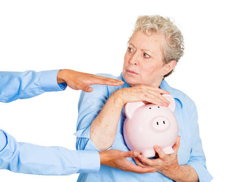 fraudulent: Closeup portrait of elderly, shocked senior business woman, grandmother, holding piggy bank, looking scared, trying to protect her savings from being stolen isolated white . Financial fraud