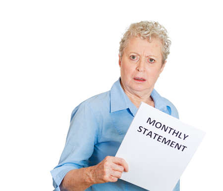bank records: Closeup portrait of sad shocked funny looking senior old woman disgusted at her monthly statement isolated white . Negative human emotion facial expression feeling. Financial crisis bad news