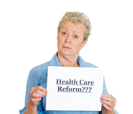 Closeup portrait of senior mature confused skeptical woman holding a sign health care reform, uncertain of universal insurance coverage, isolated white . politics, government , legislation photo
