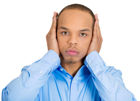 wrongful: Closeup portrait of peaceful, tranquil, looking relaxed, young corporate business man covering his ears, observing, isolated white . Hear no evil concept. Human emotions, facial expressions Stock Photo