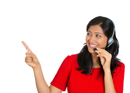 Closeup portrait of beautiful, adorable smiling female customer representative with phone headset pointing at copy space isolated on white background. Positive human emotions, facial expressions   photo