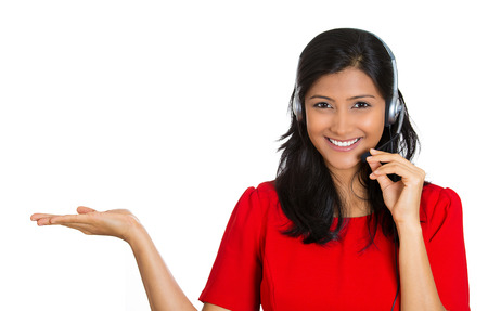 customer: Closeup portrait of beautiful, adorable smiling female customer representative with phone headset pointing at copy space isolated on white background. Positive human emotions, facial expressions