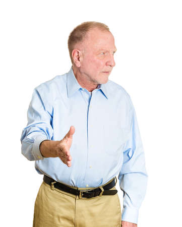 faker: Closeup portrait of sarcastic, senior mature man with bad attitude forced to extend arm for handshake, not happy about it, isolated on white background. Negative emotions, facial expression, feelings Stock Photo