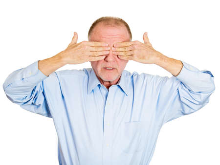 withhold: Closeup portrait of senior mature shy man closing covering eyes with hands cant see, hiding, isolated white background. See no evil concept. Negative human emotion facial expression feeling reaction Stock Photo