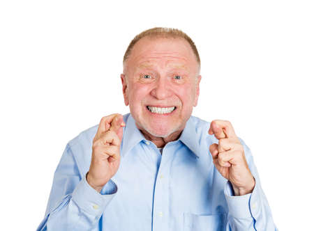crossing fingers: Closeup portrait of senior mature man crossing fingers wishing and praying for miracle, hoping for the best, isolated on white background. Positive human emotion facial expression feelings attitude