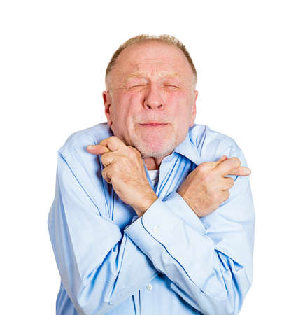 Closeup portrait of senior mature man crossing fingers wishing and praying for miracle, hoping for the best, isolated on white background. Positive human emotion facial expression feelings attitude photo