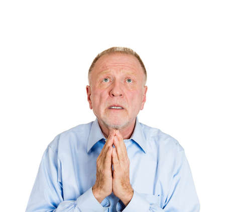 imploring: Closeup portrait of mature man praying, imploring, hands clasped, hoping for best, asking forgiveness, miracle isolated white background. Positive human emotion facial expression feelings, reaction