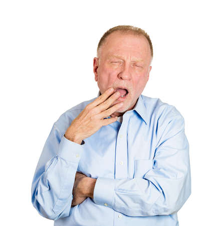 blase: Closeup portrait of funny, sleepy, senior mature business man, placing hand on mouth yawning, looking tired, isolated white background. Negative human emotion facial expression feeling, body language
