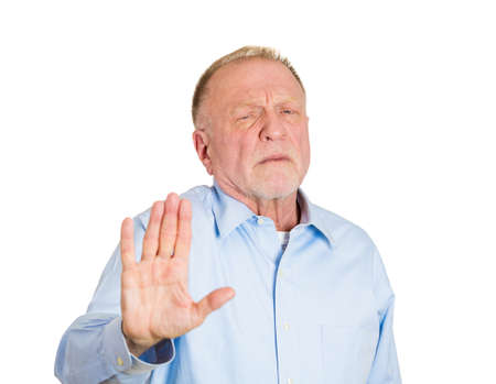 Closeup portrait of senior mature grumpy man with bad attitude giving talk to hand gesture with palm outward, isolated on white background. Negative emotions, facial expression feelings, body language photo