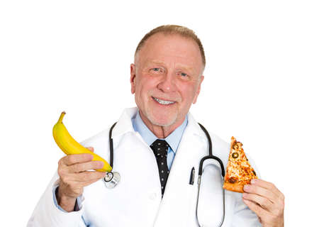 Closeup portrait of senior mature health care professional, doctor, nurse, advising you to eat fruit instead of fatty pizza, isolated on white background. Positive emotion facial expression feelings. photo