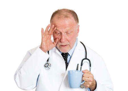 night shift: Closeup portrait of sleepy exhausted senior doctor holding cup of coffee tired, busy day night shift trying to stay awake almost asleep isolated on white background. Sleep deprivation. Face expression