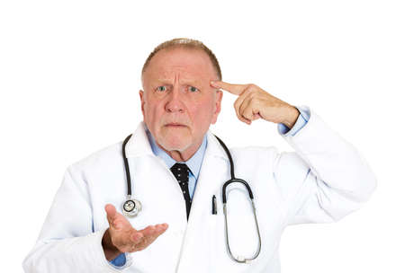 Closeup portrait of puzzled, confused senior doctor, old health care professional gesturing with finger against temple, asking question are you crazy? isolated on white background. Emotion, expression Stock Photo