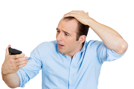 Closeup portrait of shocked man feeling head, surprised he is losing hair, receding hairline or seeing bad news on cellphone, isolated on white  Stock Photo