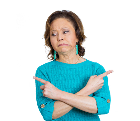 Closeup portrait of baffled senior mature woman pointing in opposite directions not sure where to go, what to do next in life, isolated on white  photo