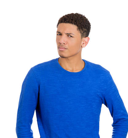 ambiguous: Closeup portrait of skeptical young man in blue shirt, looking with disbelief at you, camera gesture, isolated on white
