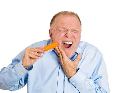 Closeup portrait senior man with sensitive tooth ache problem pain from cold frozen popsicle ice cream, hand on mouth, isolated white background. Negative human emotion, facial expressions, feelings photo