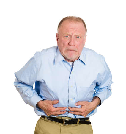 doubling: Closeup portrait old business man, elderly executive, boss, corporate worker, retired guy, unhealthy grandfather doubling over in stomach pain, isolated white background. Human emotions. Acute abdomen Stock Photo
