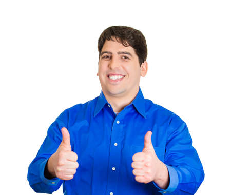 Closeup portrait, happy, handsome, young man in blue shirt showing thumbs up sign gesture, isolated white background. Positive human emotions, facial expressions, feelings, attitude, symbols