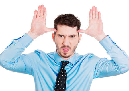 disrespectful: Closeup portrait young angry man, sticking out tongue at you, camera gesture, thumbs hands on temple, isolated white background. Negative human emotions, facial expression, feeling, attitude, reaction