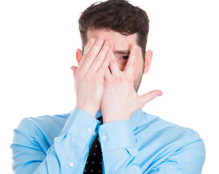 Closeup portrait of young man covering face with hands with just enough space to peek through, isolated on white background. Negative human emotion facial expression feelings, reaction.  photo