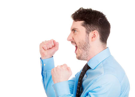 yelp: Closeup side view profile portrait of angry upset young man, worker, employee, business man fists in air, open mouth yelling, isolated on white background. Negative emotion facial expression emotion