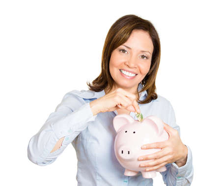 Closeup portrait of young smiling worker woman holding, depositing money into piggy bank, isolated white background. Smart currency financial investment wealth decisions. Budget management and savings photo