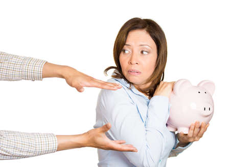 Closeup portrait of young woman, student, holding piggy bank, looking scared, angry, frustrated trying to protect her savings from being stolen, isolated on white background. Financial fraud, robbery Stock Photo