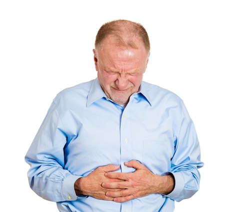 rupture: Closeup portrait old business man, elderly executive, boss, corporate worker, retired guy, unhealthy grandfather doubling over in stomach pain, isolated white background. Human emotions. Acute abdomen Stock Photo