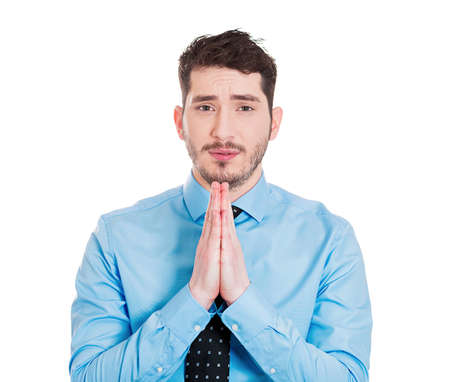 Closeup portrait of  young man gesturing with clasped hands, pretty please with sugar on top, isolated on white background. Positive emotion facial expression feelings, signs symbols, body language. photo