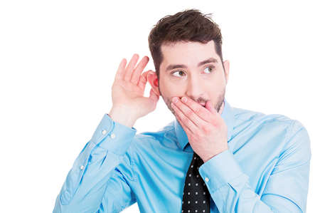 Closeup portrait of handsome, young, nosy man trying to secretly listen in on conversation, hand to mouth, surprised excited, juicy gossip he is hearing, privacy violation isolated on white background photo