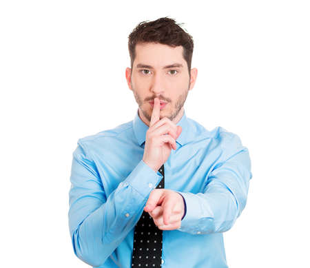 commotion: Closeup portrait of young man placing finger on lips to say, shh, be quiet, gesture with hand isolated on white background. Negative facial expression feelings emotions signs symbols, body language